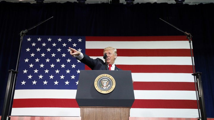 Donald Trump stands in front of an American flag.