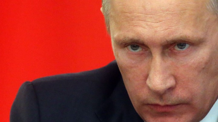 A close-up shot of Russian President Vladimir Putin's head and shoulder, against a red background