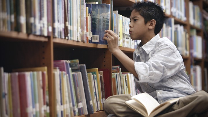 A boy looks through the shelves at a library.