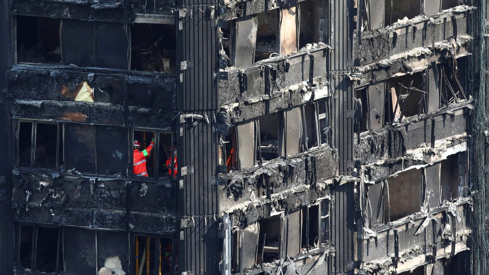 Members of the emergency services work inside burnt out remains of the Grenfell apartment tower on June 18, 2017.