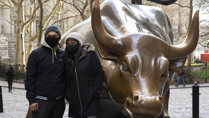 A man and a woman wear masks next to the Charging Bull statue in New York City.