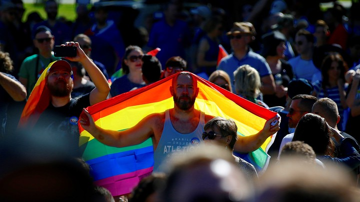 A 'Yes' campaign supporter holds a rainbow flag at a rally after it was announced that a majority of Australians support legalizing same-sex marriage at a rally in Sydney, Australia on November 15, 2017.