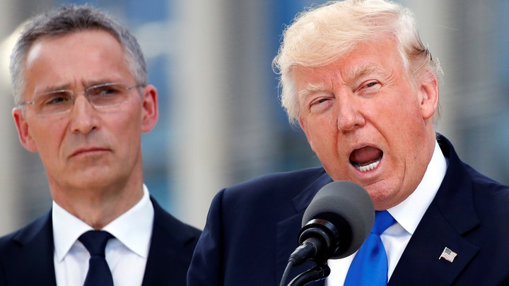 President Donald Trump speaks beside NATO Secretary General Jens Stoltenberg at the start of the NATO summit.