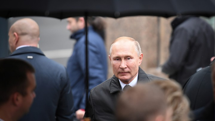 Vladimir Putin stands under an umbrella in the rain, surrounded by people facing the opposite direction.