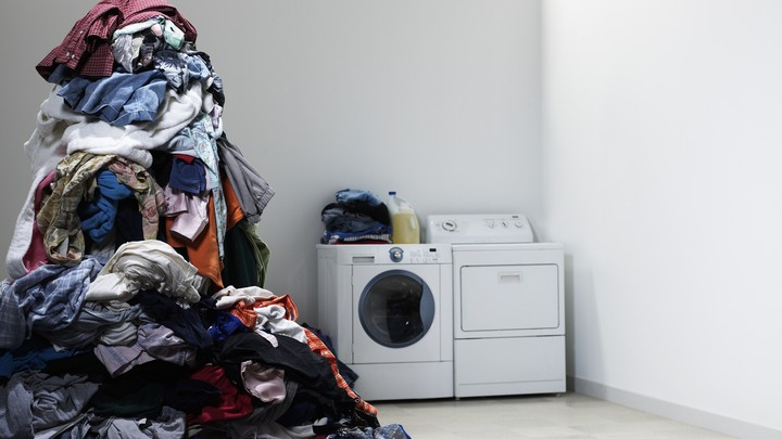 A towering pile of laundry next to a washing machine