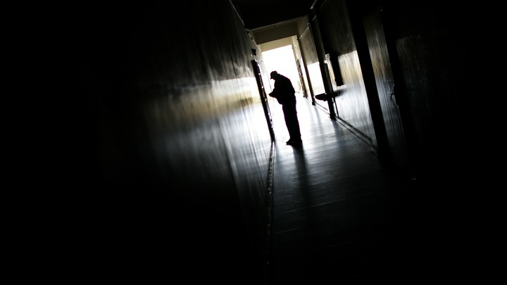 The silhouette of someone at the end of a dark hallway.