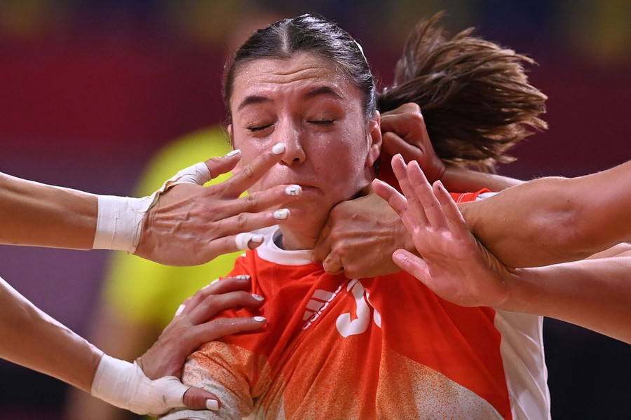 A handball player is grabbed and pushed by multiple hands.