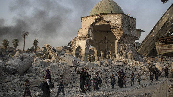 Fleeing Iraqi civilians walk past the damaged al-Nuri mosque as Iraqi forces continue their advance against ISIS militants in Mosul on July 4, 2017.