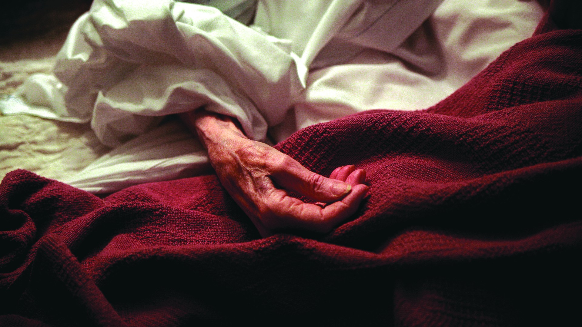 red blanket on hospital bed with an elderly hand on top