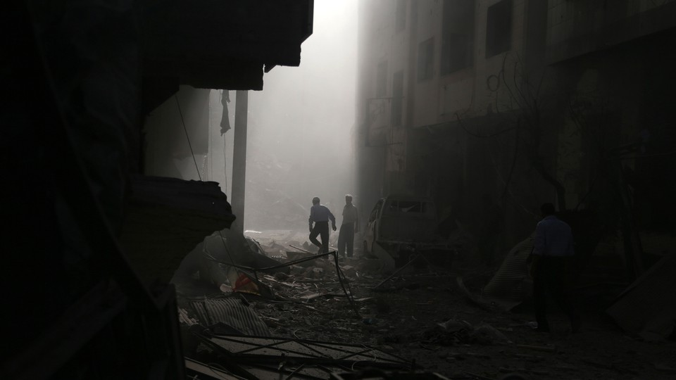 Residents inspect damage from what activists said was an air strike by forces loyal to Syrian President Bashar al-Assad on the town of Douma in Damascus, Syria, on October 2, 2015.