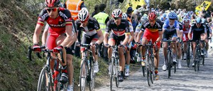 A pack of cyclists fills a country road during a race.