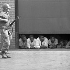 In this July 26, 1967 file photo, an Army soldier stands guard as men captured in the vicinity of the 10th Police Precinct in Detroit peer from under a garage door awaiting transfer.