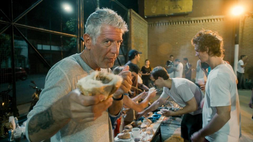 Anthony Bourdain holding part of a sandwich