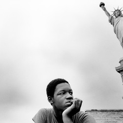 A boy sits near the Statue of Liberty.