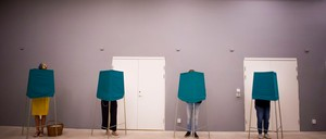 A photo of voters casting ballots from voting booths.