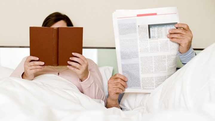 A couple sits in bed reading a newspaper and a book.