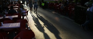 People walk down a street full of outdoor dining tables