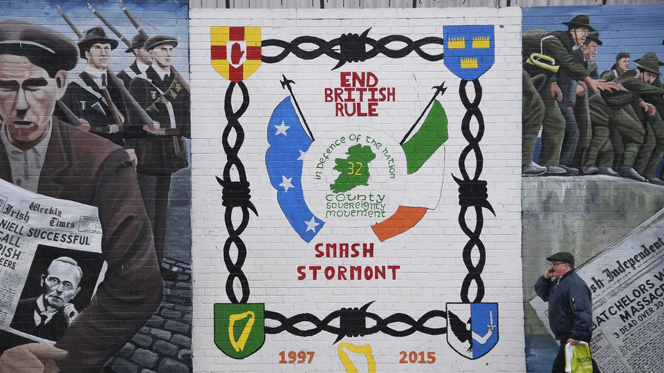 A man walks past a political mural in the Falls Road area of west Belfast, Northern Ireland, on February 28, 2017.