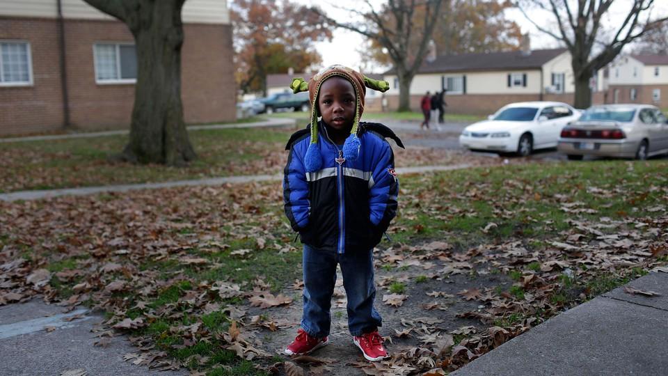 A small boy in a suburban yard