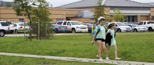 Two girls walk past a school