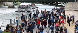 People walk in a pedestrian-only zone along the river Seine.