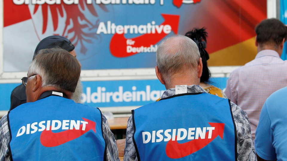 Two AfD supporters wearing the party's vests sit in front of an AfD sign.