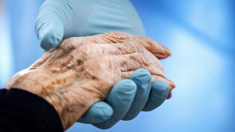 A doctor holds a patient's hand against blue background