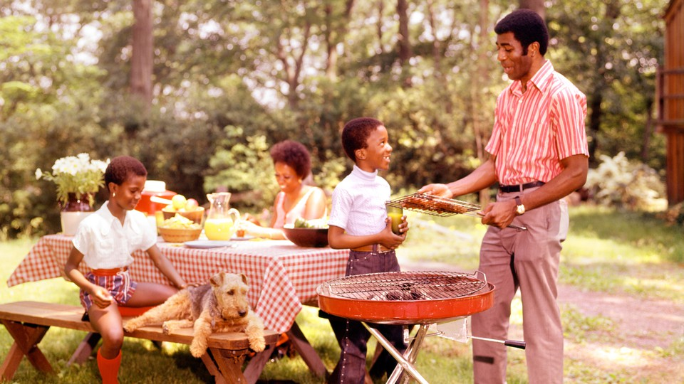 A family grills meat next to a picnic table.