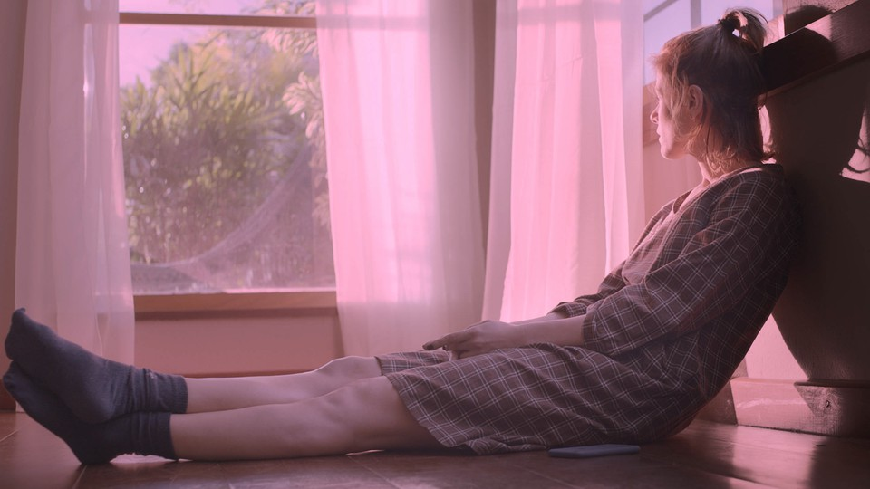 """A young woman sitting on the ground staring out the window in """"The Pink Cloud"""""""