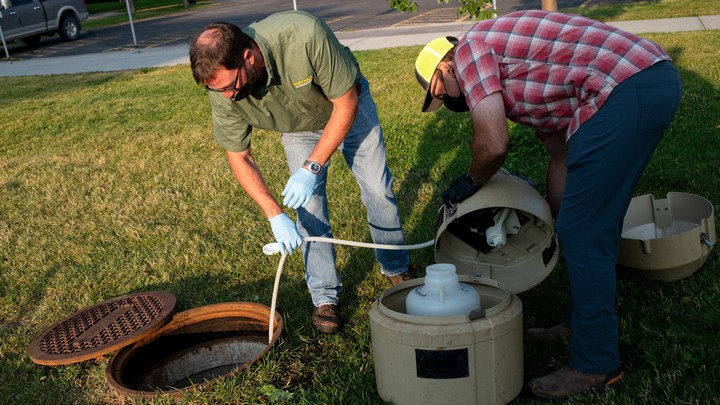 Officials collect a wastewater sample from a Montana State University sewage line.