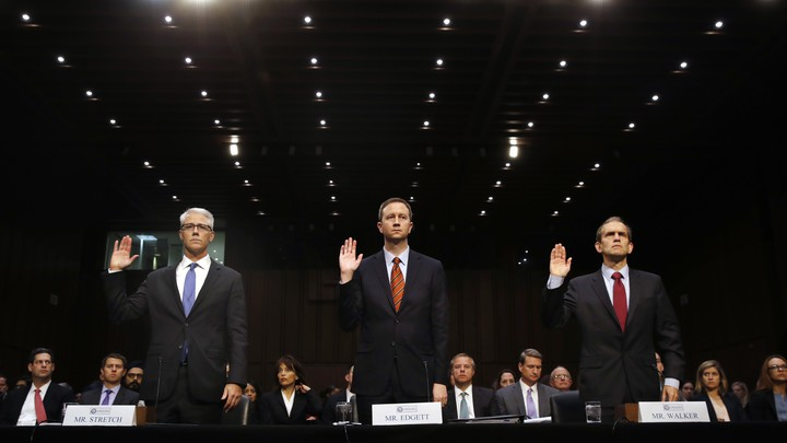 Three representatives, of Google, Facebook, and Twitter, stand with their right hands raised to be sworn in for the Senate Intelligence Committee hearing on Russia's election activity