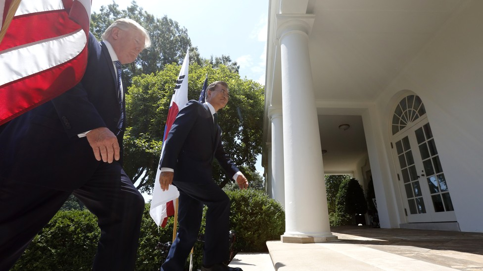 President Trump and South Korean President Moon Jae-in walk up the stairs of the rose garden with a U.S. and South Korean flag behind them.
