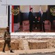 A soldier stands on a road in Syria in front of a billboard with a photo of Assad and Putin shaking hands.
