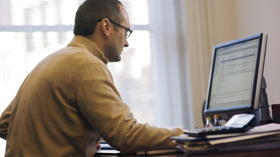 A man checks his email on his desktop computer.