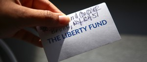 "A hand holding out a card that says ""The Liberty Fund"""