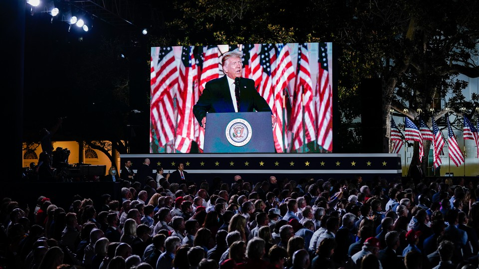 A crowd stares up at President Donald Trump while he makes a speech behind a podium. Trump is visible on a giant screen to the crowd's left.