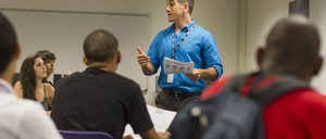 A male teacher speaks in front of a group of high school students.