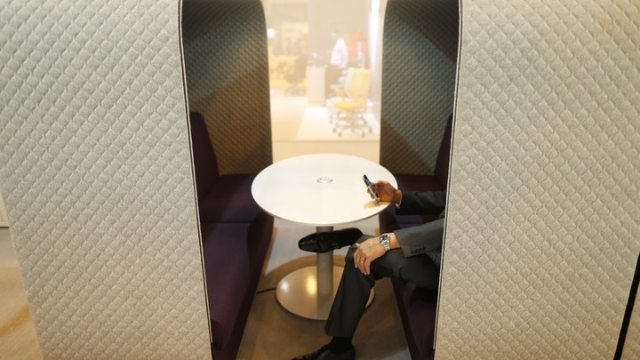A person sits at a bench surrounded by walls on three sides and uses a smartphone in front of a round table.