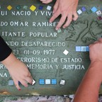 "An overhead view of hands placing squares of colored class onto rectangular, cement ""memory tile"" in Buenos Aires"