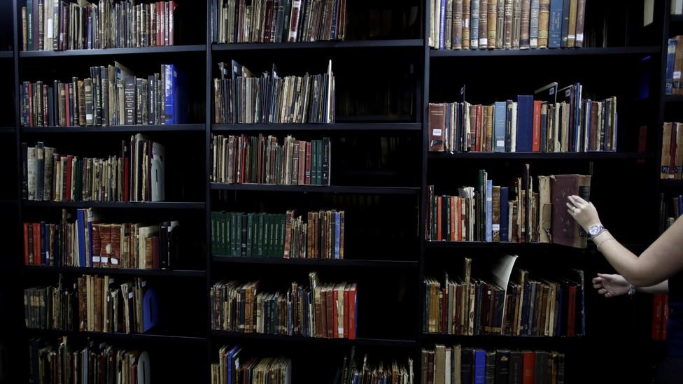 Someone takes a book off a bookshelf.