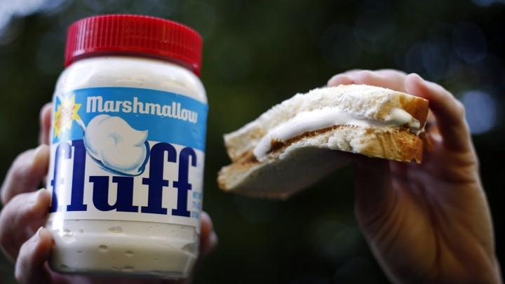A jar of fluff next to half of a peanut butter and fluff sandwich