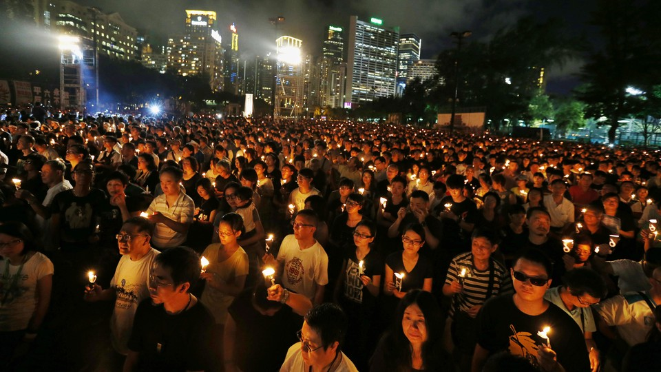 A large crowd of Hong Kong residents participates in a candlelight vigil in Victoria Park, Hong Kong.