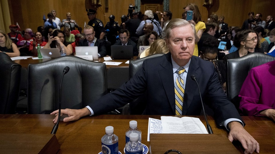 Senator Lindsey Graham sits in a hearing room as he testifies in support of his Obamacare repeal bill.