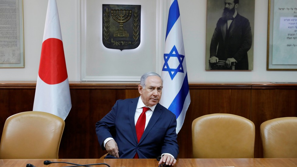 Benjamin Netanyahu sits in his office in front of a portrait of the Zionist leader Theodor Herzl.