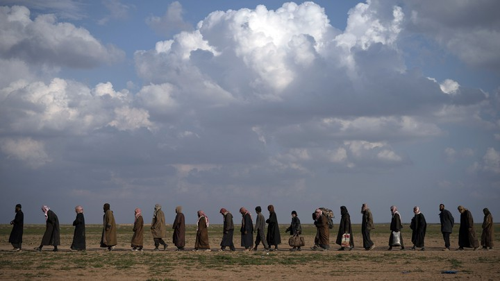 Men wait to be screened following their evacuation from Baghouz, Syria, on February 22.