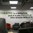 "A wall emblazoned with the quote ""Theater is a weapon, and it is the people who should wield it."""