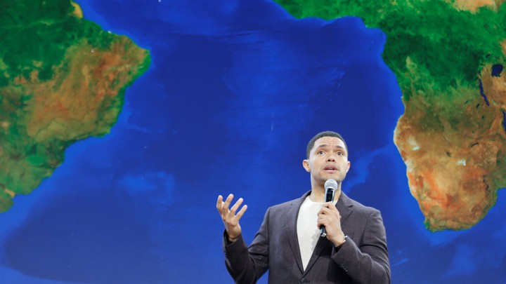 Trevor Noah stands in front of a map of Africa while speaking at a Gates Foundation event.