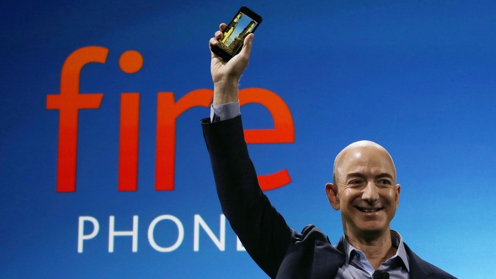 Amazon's Jeff Bezos smiles and holds a phone in the air.