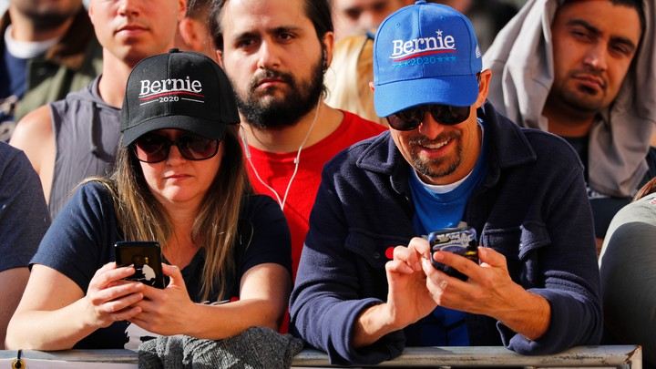 Bernie Sanders supporters look down at their phones during a rally.