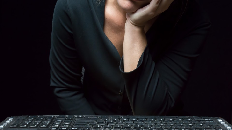 A woman rests her face on her hand while sitting in front of a computer keyboard.